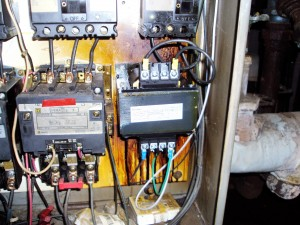 As found electrical control panel damaged and shorted out on fire tube boiler. Note discolored and streaked areas.